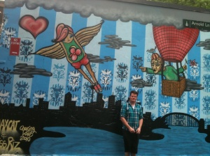 A proud big bother in front of Rhiannons artwork on a wall in Sydney